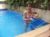 Karin inviger poolen och passar samtidigt på att rensa den från nedfallande löv och blommor...