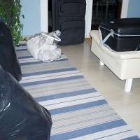 Packar lakan, täcken, kuddar och överkast i stora plastsäckar...